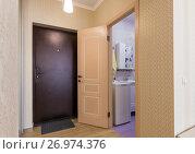 Купить «Прихожая квартиры, интерьер, входная дверь и открытая дверь в ванную комнату», фото № 26974376, снято 10 марта 2017 г. (c) Иванов Алексей / Фотобанк Лори