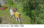 Купить «Children watering plants in the yard of country house», видеоролик № 26980748, снято 23 мая 2017 г. (c) Данил Руденко / Фотобанк Лори