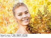 Купить «Девушка с букетом из желтых осенних листьев гуляет в лесу», фото № 26981028, снято 10 сентября 2017 г. (c) Момотюк Сергей / Фотобанк Лори