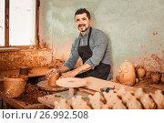 Купить «artisan man creating ceramic piece on spinning pottery wheel in workshop», фото № 26992508, снято 18 января 2019 г. (c) Яков Филимонов / Фотобанк Лори