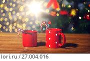 Купить «christmas candy canes and cups on wooden table», фото № 27004016, снято 1 октября 2015 г. (c) Syda Productions / Фотобанк Лори