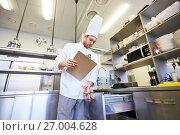 Купить «chef with clipboard doing inventory at kitchen», фото № 27004628, снято 2 апреля 2017 г. (c) Syda Productions / Фотобанк Лори