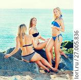 Купить «Young woman sitting on rocky beach», фото № 27005836, снято 19 сентября 2019 г. (c) Яков Филимонов / Фотобанк Лори