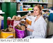 Купить «Girl seller showing different types of food for pets», фото № 27005852, снято 24 января 2020 г. (c) Яков Филимонов / Фотобанк Лори