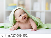 Купить «Portrait of adorable smiling baby in hooded towel lying on bed after having bathtime», фото № 27009152, снято 10 ноября 2015 г. (c) Оксана Кузьмина / Фотобанк Лори