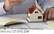 Купить «architect with house model and blueprint», видеоролик № 27010208, снято 7 сентября 2017 г. (c) Syda Productions / Фотобанк Лори