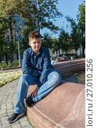 Купить «Teenager of 14 years is sitting near fountain», фото № 27010256, снято 31 августа 2017 г. (c) Володина Ольга / Фотобанк Лори