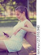 Купить «girl sitting on a bench and using mobile in garden», фото № 27010940, снято 8 июня 2017 г. (c) Яков Филимонов / Фотобанк Лори
