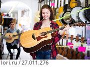 Купить «Teenage choosing best acoustic guitar», фото № 27011276, снято 14 февраля 2017 г. (c) Яков Филимонов / Фотобанк Лори