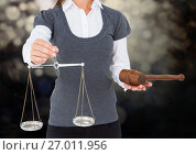 Female judge mid section with scales and gavel against dark bokeh. Стоковое фото, агентство Wavebreak Media / Фотобанк Лори