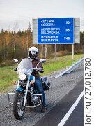 Купить «Мотоциклист на фоне указателя расстояний до города Мурманск, трасса Кола, Карелия», фото № 27012780, снято 24 сентября 2017 г. (c) Кекяляйнен Андрей / Фотобанк Лори