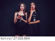 Купить «Attractive girls in the image of vampires hold glasses with blood. Halloween.», фото № 27026864, снято 22 сентября 2017 г. (c) Женя Канашкин / Фотобанк Лори
