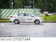 Такси Uber на фоне типичной для Москвы зеленой полосатой ограды (2017 год). Редакционное фото, фотограф Сайганов Александр / Фотобанк Лори