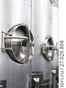 A lot of stainless steel tanks with large round hatches, modern beverage production. Стоковое фото, фотограф Андрей Радченко / Фотобанк Лори