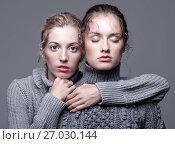 Купить «Two young women in gray sweaters on grey background. Beautiful girls stretching hands forward in embrace. One girl with eyes closed», фото № 27030144, снято 26 июля 2017 г. (c) Serg Zastavkin / Фотобанк Лори