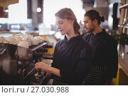 Купить «Young wait staff using espresso maker at coffee shop», фото № 27030988, снято 21 мая 2017 г. (c) Wavebreak Media / Фотобанк Лори