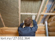 Купить «Worker installing insulation panels of mineral wool into roof of house. Roofing construction and thermal protection», фото № 27032364, снято 3 июня 2016 г. (c) Сергей Дорошенко / Фотобанк Лори