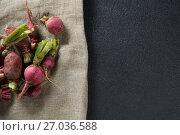 Купить «Overhead view of red radishes on burlap over slate», фото № 27036588, снято 12 июня 2017 г. (c) Wavebreak Media / Фотобанк Лори