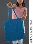 Купить «Mid section of young woman holding blue shopping bag», фото № 27037952, снято 16 мая 2017 г. (c) Wavebreak Media / Фотобанк Лори