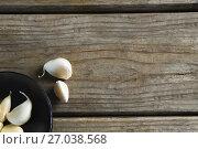 Купить «Garlics in plate on wooden table», фото № 27038568, снято 5 июня 2017 г. (c) Wavebreak Media / Фотобанк Лори