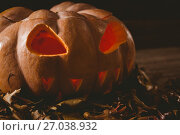 Купить «Close up of jack o lantern with leaves on table during autumn», фото № 27038932, снято 26 мая 2017 г. (c) Wavebreak Media / Фотобанк Лори