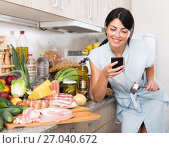 Купить «Cheerful woman is chatting by phone in time cooking on the kitchen», фото № 27040672, снято 16 июля 2019 г. (c) Яков Филимонов / Фотобанк Лори