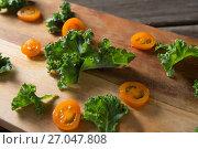 Купить «Close up of kale and tomato slices on cutting board», фото № 27047808, снято 12 июня 2017 г. (c) Wavebreak Media / Фотобанк Лори