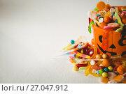 Купить «Orange bucket with various sweet food during Halloween on white background», фото № 27047912, снято 26 мая 2017 г. (c) Wavebreak Media / Фотобанк Лори