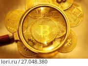 Золотые монеты криптовалюты Биткоин под увеличительным стеклом. Стоковое фото, фотограф Николай Винокуров / Фотобанк Лори