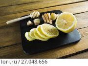 Купить «Lime, garlic and honey dipper in black slate plate», фото № 27048656, снято 5 июня 2017 г. (c) Wavebreak Media / Фотобанк Лори