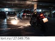 Купить «Мотоцикл с заведенным двигателем на темной площадке паркинга», фото № 27049756, снято 1 октября 2017 г. (c) Кекяляйнен Андрей / Фотобанк Лори