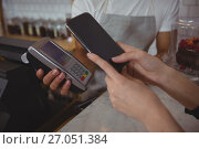 Cropped hand of customer making contactless payment with waiter holding credit card reader. Стоковое фото, агентство Wavebreak Media / Фотобанк Лори