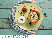 Купить «Plate of breakfast cereal with fruits and yoghurt on wooden table», фото № 27051796, снято 13 июня 2017 г. (c) Wavebreak Media / Фотобанк Лори