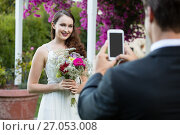 Купить «Bridegroom photographing bride holding bouquet at park», фото № 27053008, снято 2 мая 2017 г. (c) Wavebreak Media / Фотобанк Лори