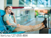 Young man in an airport lounge waiting for flight aircraft. Caucasian man with smartphone indoor. Стоковое фото, фотограф Дмитрий Травников / Фотобанк Лори