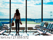 Купить «Young woman in international airport with her luggage background big window. Airline passenger in an airport lounge waiting for flight aircraft», фото № 27059572, снято 10 июня 2015 г. (c) Дмитрий Травников / Фотобанк Лори