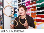 Купить «Senior woman choosing embroidery hoops for fancywork», фото № 27060972, снято 10 мая 2017 г. (c) Яков Филимонов / Фотобанк Лори