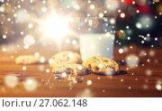 Купить «close up of cookies and milk over christmas lights», фото № 27062148, снято 1 октября 2015 г. (c) Syda Productions / Фотобанк Лори