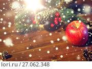 Купить «close up of apple with fir decoration on wood», фото № 27062348, снято 1 октября 2015 г. (c) Syda Productions / Фотобанк Лори