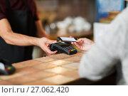Купить «hands with payment terminal and smartphone at bar», фото № 27062420, снято 8 декабря 2016 г. (c) Syda Productions / Фотобанк Лори