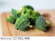 Купить «close up of broccoli on wooden cutting board», фото № 27062448, снято 21 февраля 2017 г. (c) Syda Productions / Фотобанк Лори