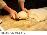 Купить «baker portioning dough with bench cutter at bakery», фото № 27062512, снято 15 мая 2017 г. (c) Syda Productions / Фотобанк Лори