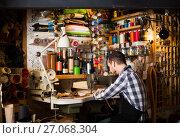 Купить «male worker sewing stitches on belt in leather workshop», фото № 27068304, снято 22 марта 2019 г. (c) Яков Филимонов / Фотобанк Лори