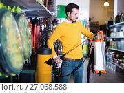 Купить «Young man choosing garden sprayer in garden equipment shop», фото № 27068588, снято 2 марта 2017 г. (c) Яков Филимонов / Фотобанк Лори
