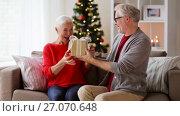 Купить «happy smiling senior couple with christmas gift», видеоролик № 27070648, снято 20 сентября 2017 г. (c) Syda Productions / Фотобанк Лори
