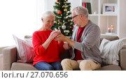 Купить «happy smiling senior couple with christmas gift», видеоролик № 27070656, снято 20 сентября 2017 г. (c) Syda Productions / Фотобанк Лори