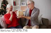 Купить «happy smiling senior couple with christmas gift», видеоролик № 27070716, снято 20 сентября 2017 г. (c) Syda Productions / Фотобанк Лори