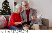 Купить «happy senior couple with tablet pc at christmas», видеоролик № 27070744, снято 20 сентября 2017 г. (c) Syda Productions / Фотобанк Лори