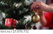 Купить «senior woman hands decorating christmas tree», видеоролик № 27070772, снято 3 октября 2017 г. (c) Syda Productions / Фотобанк Лори