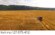 Купить «The combine harvests wheat, in the distance mountains and bales of hay», видеоролик № 27075412, снято 17 августа 2015 г. (c) Владимир Кравченко / Фотобанк Лори